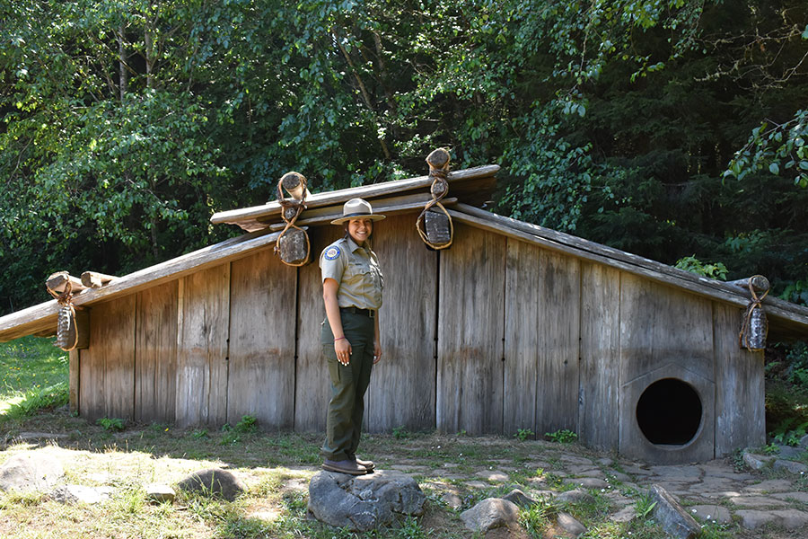 Park ranger Maiya beside a living house, Sumeg Village